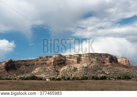 Cliffs Of The Colorado National Monument Under A Summer Sky With Cumulus Clouds And Virga Near Grand