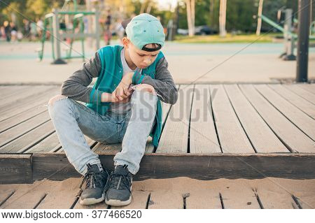 Childhood Knee Injuries. Beaten Knees In The Sports Field. A Teenager In A Cap Tore His Jeans And In
