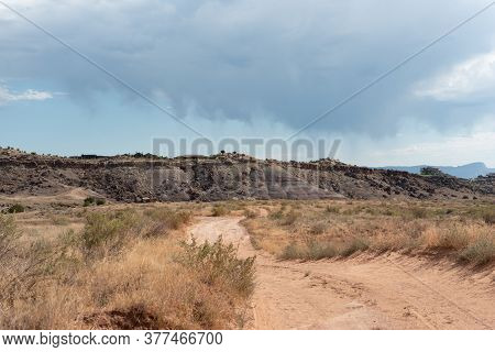 Rough Desert Road With Ragged Dark Clouds In A Summer Sky