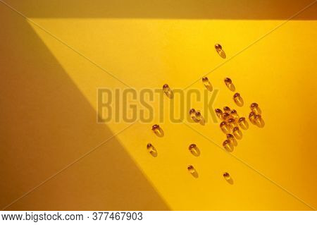Vitamin D Concept In The Sunlight. Vitamin Gelatin Capsules In A Ray Of Light
