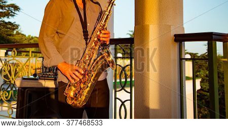 Hands Of A Musician, While Playing The Golden Saxophone, In A Summer Restaurant
