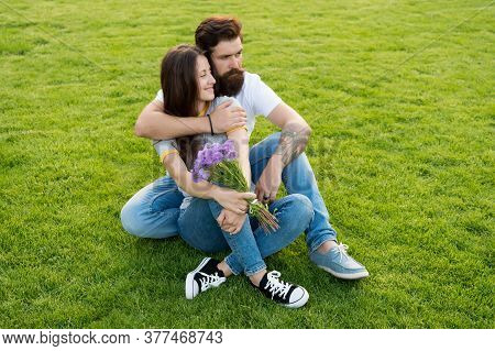 Romantic Getaway. Couple In Love Relax On Green Grass. Sexy Woman And Bearded Man Enjoy Summer Day.