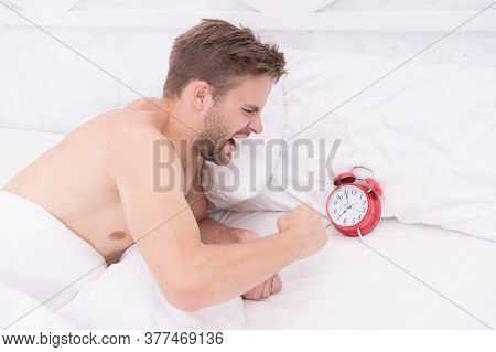 He Is Late. Angry Guy Break Alarm Clock In Bed. Unshaven Man Awake From Sleep. Keeping Late Hours. W