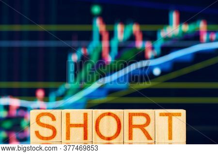 Short. Wooden Blocks With The Inscription Short On The Background Of The Stock Chart