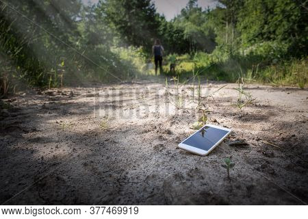 Lost Smartphone On The Ground, People In Background. Geting Lost In The Forest