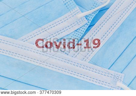Covid-19  Word On A Heap Of Blue Surgical Face Masks - Coronavirus, Covid-19 Concept.