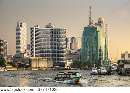 Bangkok Skyline And Traffic On Chao Phraya River As Seen From A Boat At Sunset