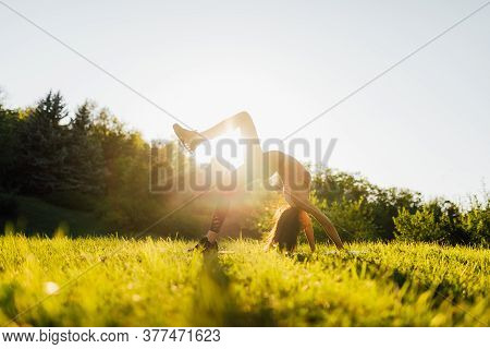 Young Woman Doing Yoga In Morning Park. Young Female Exercising Vital Fitness At Outdoors Nature Wit
