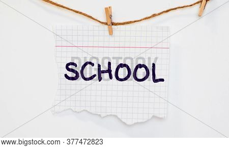 The Word School On Small Pieces Of Paper On A Blue Background .the Concept Of The School.september.a