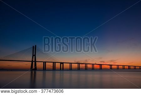 Beautiful Sunrise At Vasco Da Gama Bridge, The Longest Bridge In Europe, Who Spans The Tagus River I