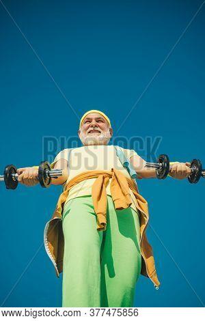 Old Mature Man Exercising With Dumbbell. Senior Sportsman In Sport Center. Like Sports. Elderly Man