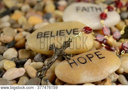 Worded Stones With A Rosary To Bring Meaning To The Faith Of Jesus Christ.