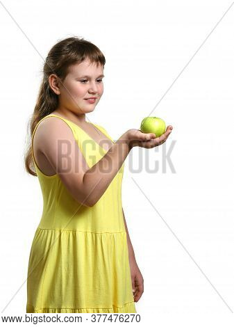 Chubby Smiling Girl In Yellow Sundress Stands And Holds Green Apple In Her Right Hand And Looks At I