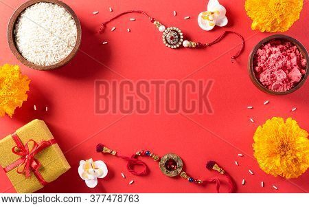 Raksha Bandhan, Indian Festival With Beautiful Rakhi And  Rice Grains On Red Background.  A Traditio