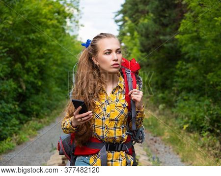 Portrait Of A Hiker Woman Lost In Forest. She Using Mobile Gps Map.