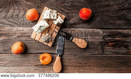 Tasty Blue Cheese With Peaches Fruit On A Wooden Background. Dorblu Cheese Pieces, Danish Blue Chees