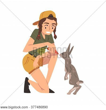Female Zoo Worker Feeding Rabbit With Fresh Carrot, Veterinarian Or Professional Zookeeper Character