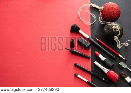Make-up Products And Xmas Decoration Against Red And Black Background, Copy Space