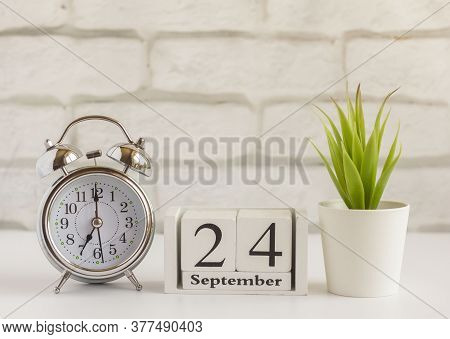 September 24 On A Wooden Calendar On A Table Or Shelf Next To An Alarm Clock.one Day Of The Autumn M