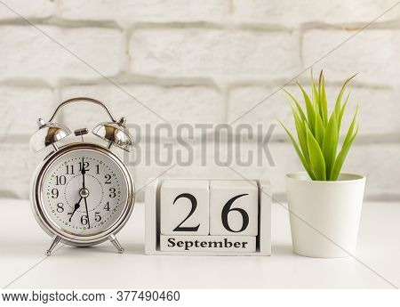 September 26 On A Wooden Calendar On A Table Or Shelf Next To An Alarm Clock.one Day Of The Autumn M