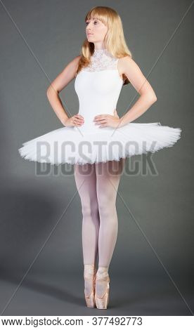 Young female ballet dancer in wearing tutu tiptoeing over grey background