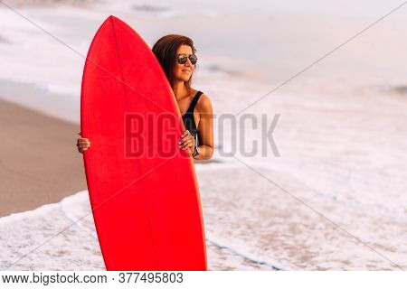 Beautiful Sexy Surfer Girl On The Beach At Sunset. Beautiful Girl With A Surfboard. Attractive Sexy
