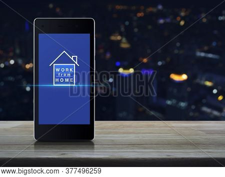 Work From Home Flat Icon On Modern Smart Mobile Phone Screen On Wooden Table Over Blur Colorful Nigh