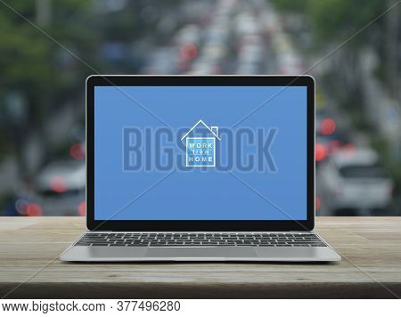 Work From Home Flat Icon With Modern Laptop Computer On Wooden Table Over Blur Of Rush Hour With Car