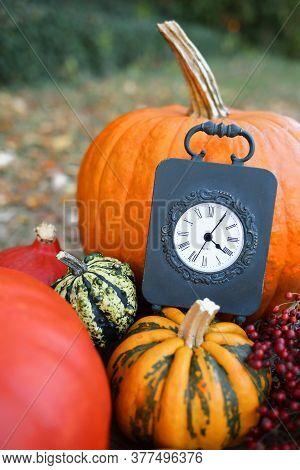 Autumn Time. Thanksgiving Holiday. Pumpkin Harvest. Vintage Black Clock, Pumpkin Assortment On Blurr