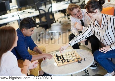 multiethnic group of business people playing chess while having a break in relaxation area at modern startup office