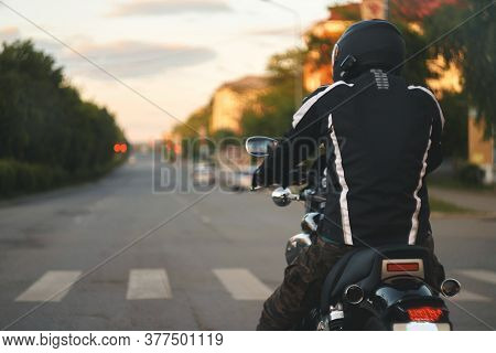 A Motorcyclist Stands At A Traffic Light