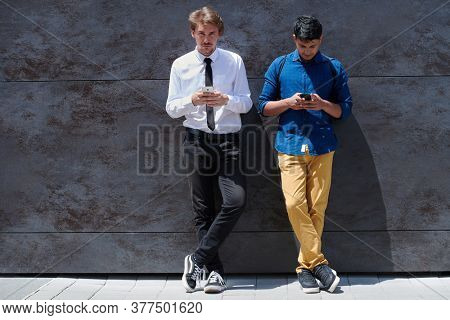 casual multiethnic startup business men one of them is indian using mobile phone during break from work in front of gray wall outside