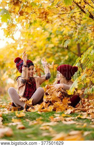Two Little Girls In The Hat Sitting On The Ground Under The Trees In Autumn Park With Maple Leaf In