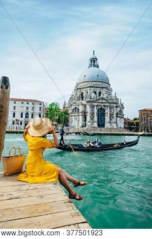Woman In Yellow Sundress Sitting On Pier With View Of Grand Canal