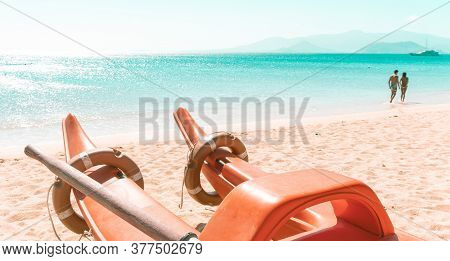 Rescue Boat Close-up On A Sandy Tropical Beach. A Young Couple Is Walking Along The Seashore With Aq