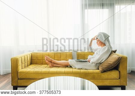 Woman In White Bath Robe And Towel On Her Head Is Sitting On Yellow Sofa And Working From Home, Usin