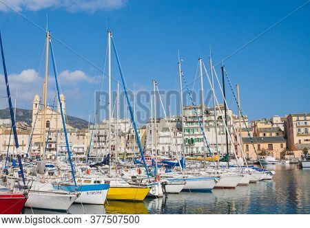 Bastia, Corsica, France March 4 2012: Colorful Port Of Bastia With Boats, Buildings And Church View