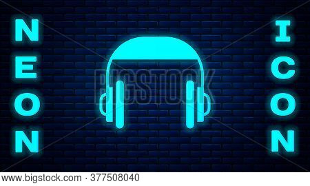 Glowing Neon Headphones Icon Isolated On Brick Wall Background. Support Customer Service, Hotline, C