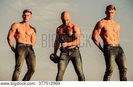 Strong Men Blue Sky Background. Showing Abs Biceps. Group Muscular Men Outdoors. Athletic Bodybuilde