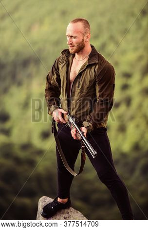 Man Brutal Poacher With Weapon Natural Landscape Background. Hunter Poacher Looking For Victim. Hunt