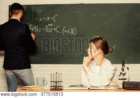Teacher And Student Near Chalkboard. College University Education. High School. Solving Task. Man Wr