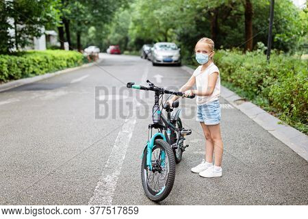 Active School Kid Girl In Medical Mask Riding A Bike On Summer Sunny Day. Happy Child Biking During