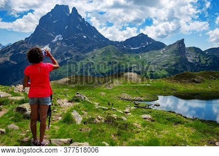 Hiking Woman Drinking A Water And Looking Pic Du Midi Ossau In French Pyrenees Mountains