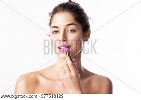 Beauty Shot Of Young Woman With Flawless Skin Applying Purple Lipstick. Isolated On White Background