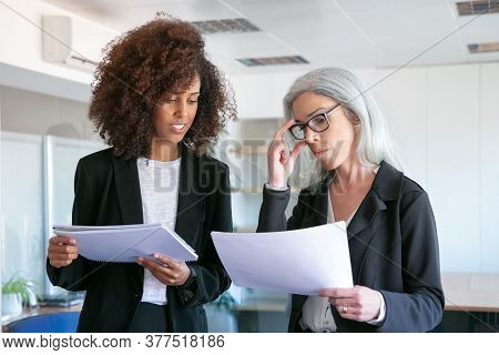 Content Manager In Glasses Reading Document With Young Colleague. Two Successful Content Businesswom