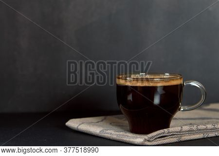 Glass Cup Of Hot Fresh Coffee, Brew From Arabica, With Thick Golden Foam Froth On Dark Background. E