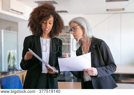 Content Young Manager Showing Document To Adult Colleague. Two Pretty Content Female Colleagues Hold