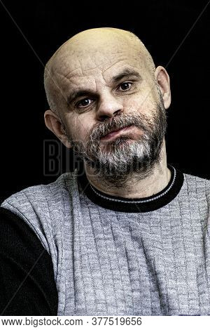 Portrait Of A Bald Man With A Gray Beard With Swollen Cheeks On The Dark Background