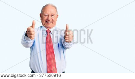 Senior handsome grey-haired man wearing elegant tie and shirt approving doing positive gesture with hand, thumbs up smiling and happy for success. winner gesture.