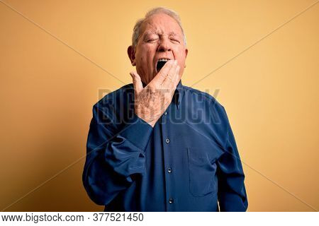 Grey haired senior man wearing casual blue shirt standing over yellow background bored yawning tired covering mouth with hand. Restless and sleepiness.